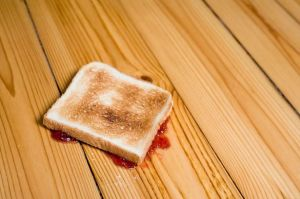 Slice-of-toast-with-strawberry-jam-upside-down-on-floor