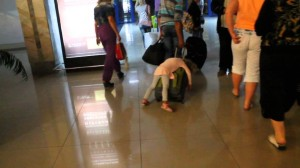 tired-girl-hitches-a-ride-on-her-fathers-suitcase-1024x576